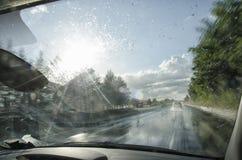 Coche que va rápidamente en una autopista mojada Imagenes de archivo
