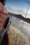 Coche que vadea a través del camino pesadamente inundado. Fotografía de archivo