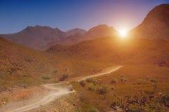 Coche que viaja en el camino en las montañas Imagenes de archivo