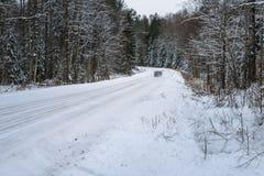 coche que viaja en el camino forestal nevoso entre los árboles imagen de archivo