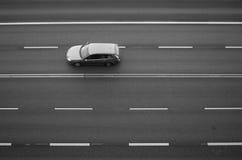 Coche que viaja en un camino vacío Imagen de archivo libre de regalías