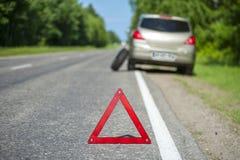 Coche quebrado en el borde de la carretera, el triángulo rojo y la rueda de repuesto Fotos de archivo