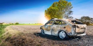 Coche quemado abandonado en el campo aislado Imagen de archivo