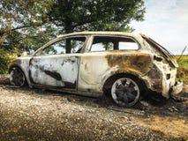 Coche quemado abandonado en el campo aislado Imágenes de archivo libres de regalías