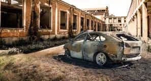 Coche quemado abandonado en la ruina aislada Fotografía de archivo