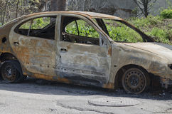 Coche quemado parqueado en la vista lateral de la calle - foto ascendente cercana de un coche del quemar Imagen de archivo libre de regalías