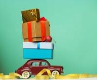 Coche retro azul del juguete que entrega los regalos de la Navidad o del Año Nuevo, en amarillo Fotografía de archivo libre de regalías