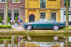 Coche retro obsoleto anticuado junto con Person Riding una bicicleta imagenes de archivo