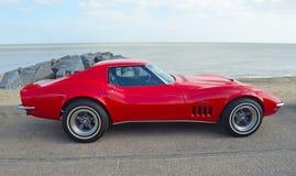 Coche rojo clásico de motor de la pastinaca de Chevrolet Corvette parqueado en la 'promenade' de la orilla del mar Fotos de archivo