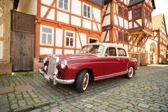 Coche rojo de Mercedes de la vendimia delante de la casa Imágenes de archivo libres de regalías