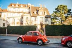 Coche rojo de Volkswagen Beetle del vintage en la calle Imágenes de archivo libres de regalías