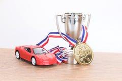 Coche rojo del juguete con el trofeo que se divierte de plata imagen de archivo libre de regalías