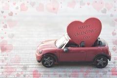 Coche rojo del juguete que entrega el corazón del día del ` s de la tarjeta del día de San Valentín foto de archivo libre de regalías