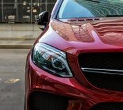 coche rojo del prestigio en el estacionamiento del edificio fotografía de archivo libre de regalías