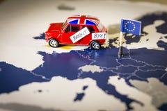 Coche rojo del vintage con palabras de la bandera y del brexit o del adiós de Union Jack sobre un mapa y bandera de UE Foto de archivo libre de regalías