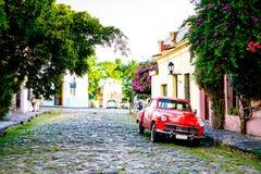 Coche rojo del vintage en la calle cobbled durante puesta del sol, árboles Imágenes de archivo libres de regalías