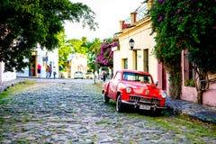 Coche rojo del vintage en la calle cobbled durante puesta del sol, árboles Fotografía de archivo