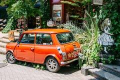 Coche rojo delante de la tienda del vintage en el pueblo floral de Yufuin, Japón Imagen de archivo