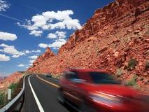 Coche rojo en el camino en Arizona Foto de archivo libre de regalías