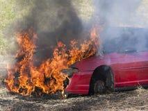 Coche rojo en el fuego imagen de archivo libre de regalías