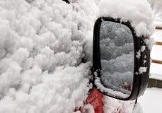 Coche rojo nevado parqueado afuera, espejo de la vista posterior, desafío del transporte del invierno fotos de archivo libres de regalías