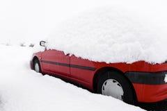 Coche rojo sitiado por la nieve Foto de archivo libre de regalías