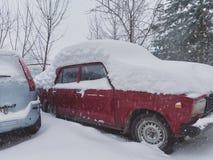 Coche ruso viejo debajo de la nieve acumulada por la ventisca Foto de archivo