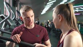 Coche sonriente hermoso que habla con la mujer deportiva joven en el gimnasio metrajes