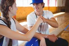 Coche sonriente que hace el topetón del puño con el jugador de básquet de sexo femenino Imagenes de archivo