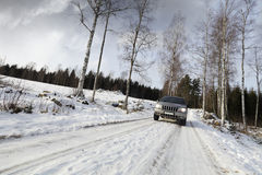 Coche, suv, conduciendo en el camino nevoso Imagen de archivo libre de regalías
