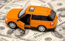 Coche SUV del juguete en el fondo del dólar Imágenes de archivo libres de regalías