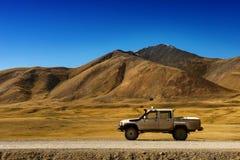 Coche SUV en el fondo de las montañas Imágenes de archivo libres de regalías
