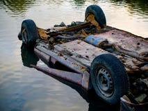 Coche vaciado oxidado en la charca de agua Imágenes de archivo libres de regalías
