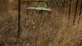 Coche verde abandonado viejo oxidado que miente en un campo de hierba alto detrás de la cerca tiro Vehículo ruso oxidado arruinad metrajes