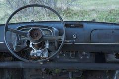 Coche viejo abandonado, tablero de instrumentos y volante Foto de archivo libre de regalías