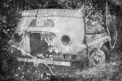 Coche viejo que aherrumbra en bosque Imagen de archivo