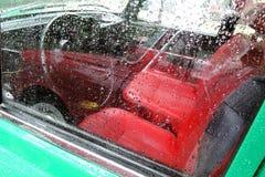 Coche viejo Sillas y rueda rojas La ventana es cubierta por las gotas de agua Fotos de archivo libres de regalías
