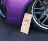 Coche violeta en un salón del automóvil con un tablón de madera divertido cerca de la rueda Fotografía de archivo libre de regalías