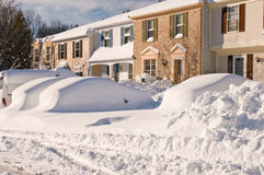 Coche y casas después de la tempestad de nieve Imagenes de archivo