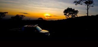Coche y cielo en la puesta del sol Fotografía de archivo