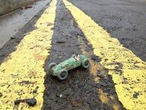 Coche y conductor de competición del juguete del vintage, con pátina original de la pintura verde gastada, entre la línea amarill Foto de archivo