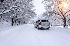 Coche y nieve que cae en invierno en el camino forestal con mucha nieve Imagen de archivo