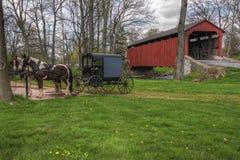 Cochecillo de Amish estacionado por el puente cubierto Fotos de archivo