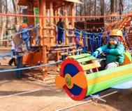 Cochecillo que monta del niño pequeño en parque de la aventura Imagenes de archivo