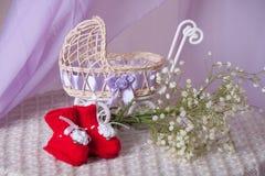 Cochecito de bebé, botines y ramo de la primavera Imágenes de archivo libres de regalías