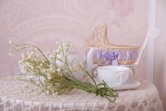 Cochecito de bebé, taza de té y composición del ramo de la primavera Fotografía de archivo