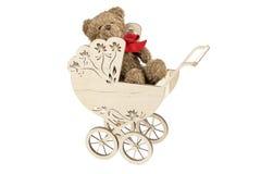 Cochecito de niño de madera con el oso de peluche Fotos de archivo