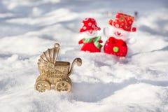 Cochecito del Año Nuevo con un recién nacido en un fondo de un par de muñecos de nieve felices Foto de archivo libre de regalías