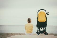 Cochecito siguiente que se sienta de la madre joven por el mar Foto de archivo libre de regalías