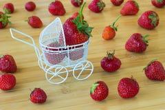 Cochecito y fresas de bebé en la tabla Foto de archivo libre de regalías